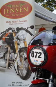 Doc Jensens Le Mans 2 Classic Racer mit Startnummer vom Stadtparkrennen 2014 vor dem Doc Jensen Guzzi Plakat